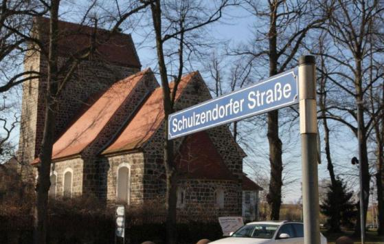 Straßenschild und Kirche der Schulzendorfer Straße beim Flughafenparkplatz Mein Parken Berlin Brandenburg (BER)
